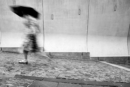 woman running in the rain, outside scottish parliament